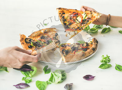 People's hands taking pieces of Freshly baked vegetarian pizza