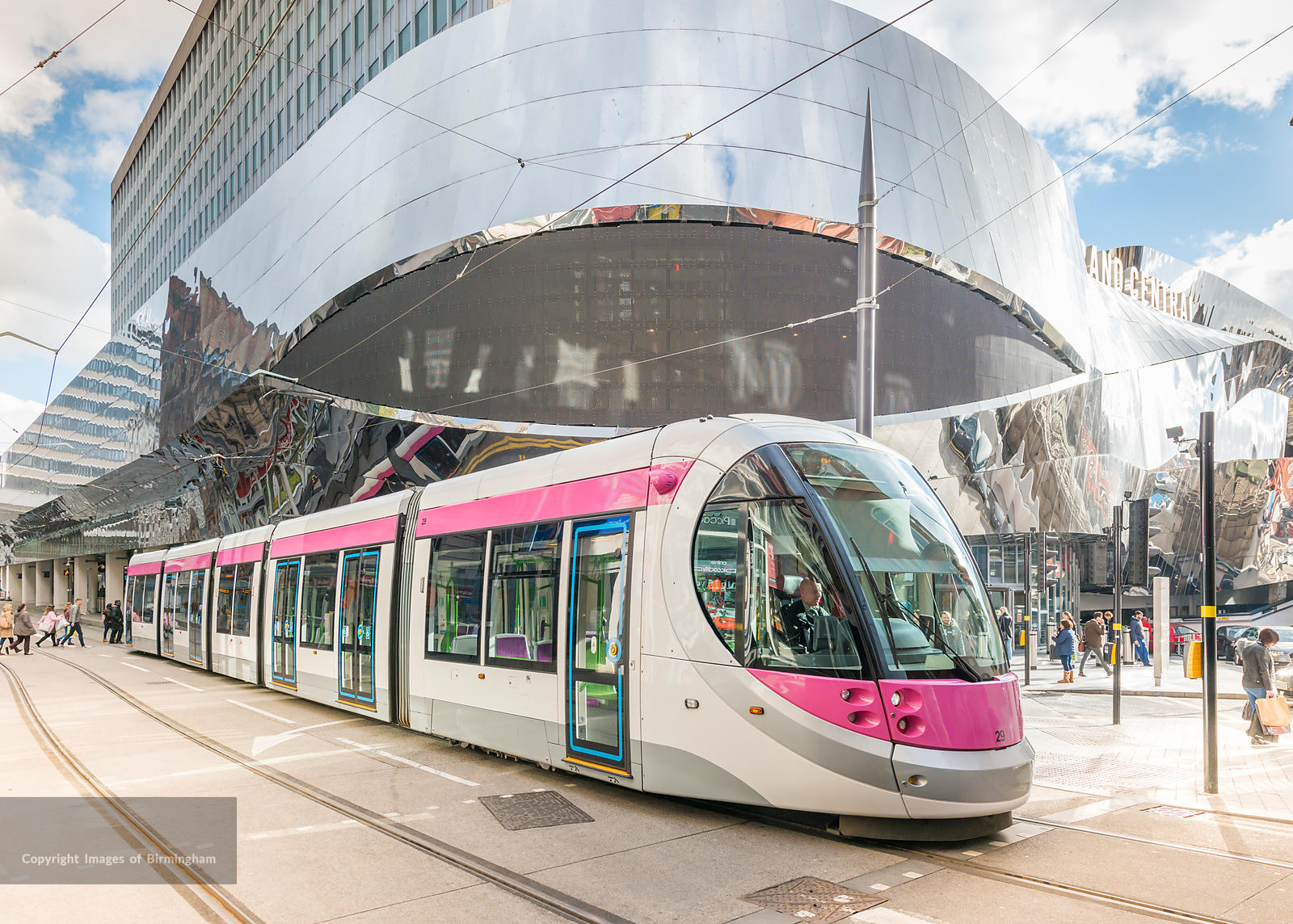 A tram in Birmingham City Centre alongside New Street train station, England.