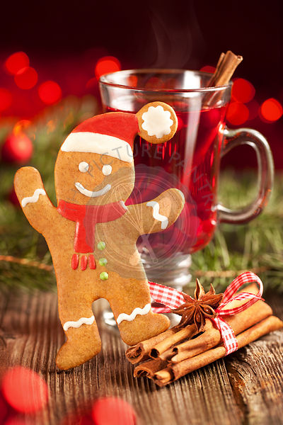 Smiling gingerbread man and glass of mulled wine with berries and spices.