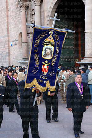 Member of the Brotherhood of Knights of the Lord of the Holy Sepulchre carrying banner outside La Merced church at start of Good Friday procession , Cusco , Peru