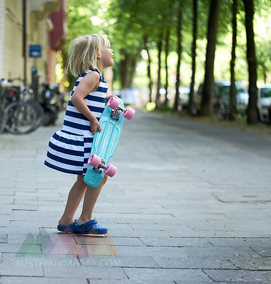 Happy little girl with skateboard on pavement