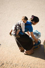 Luang Prabang, Laos - A young mother with her child strapped to her back.