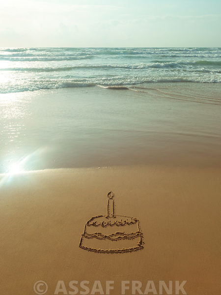 Cake with candles drawn on the beach
