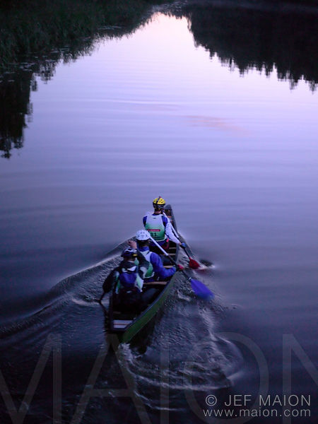 Adventure racing competitors in canoe at dusk