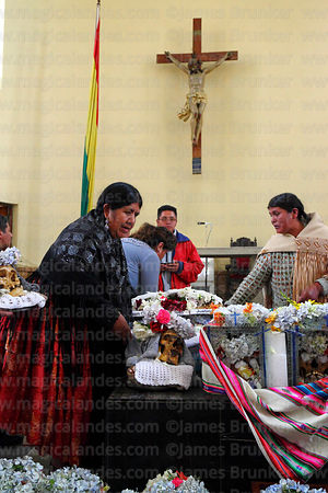 People placing their skulls in front of altar in church before mass, Ñatitas festival, La Paz, Bolivia