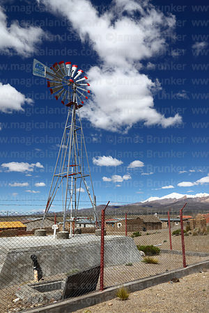 Small windmill for pumping water with Agua Sustentable / Sustainable Water written on vane , Lagunas, Sajama National Park, Bolivia