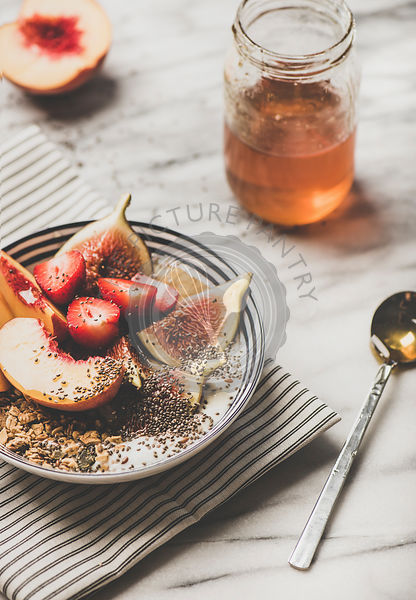 Healthy summer vegetarian breakfast bowl with yogurt, fruits and honey