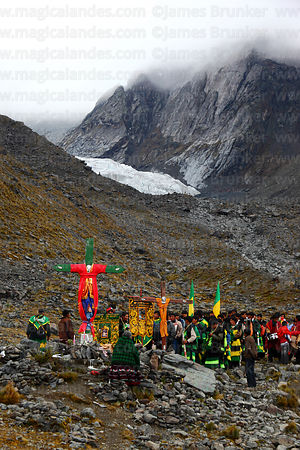 Spiritual leaders praying at cross before making pilgrimage up mountainside to glaciers, Qoyllur Riti festival, Peru