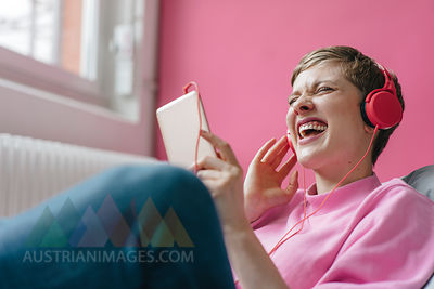Screaming woman with cell phone and headphones listening to music