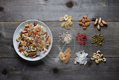 White ceramic bowl full with a healthy trail mix of dried fruits, nuts and seeds. Shot areal view with ingredients seporated and laying on the rustic wood surface.