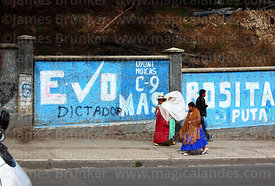 Aymara women walking past Evo Morales election propaganda, La Paz, Bolivia