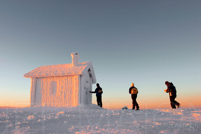 Hikers by winter wilderness hut