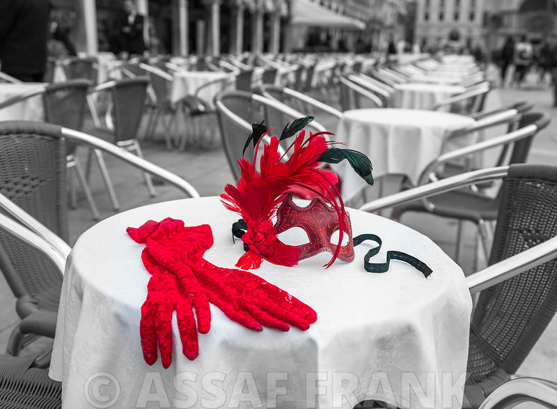 Female hand gloves with Venetian mask on cafe table, Venice, Italy
