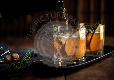 Whiskey cocktail with fresh thyme and pear on a rustic wood background.