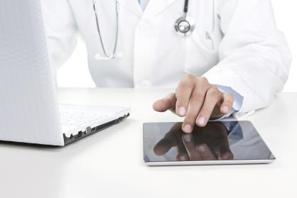 Close-up of a Doctor Using a Laptop and a Tablet