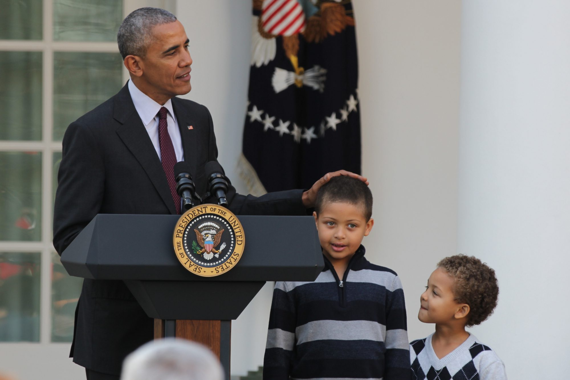 """Unlike Malia and Sasha, the young boys """"have not yet been turned cynical by Washington,"""" Obama says, placing his hand on top of his nephew's head."""