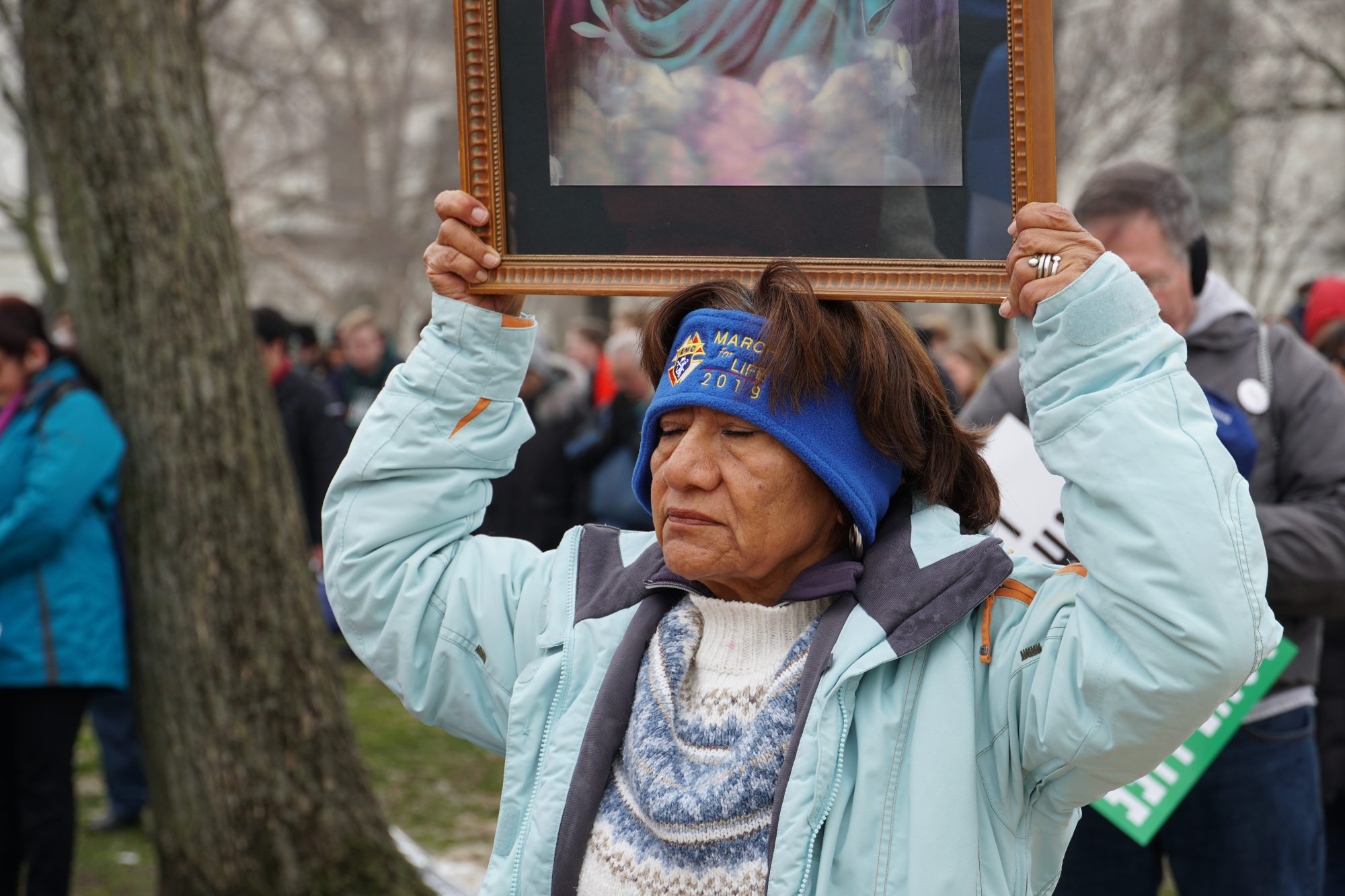 A woman holds up an image of Jesus during the prayer. (Ester Wells/MNS)