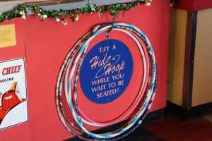 """At the hostess station, diners can hula-hoop while waiting for a seat. The servers' shirts have diner puns like """"Give up carbs? Over my bread body."""" (Charlotte Walsh/MNS)"""