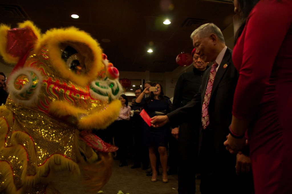 Raymond Chin feeds a red envelope to a lion