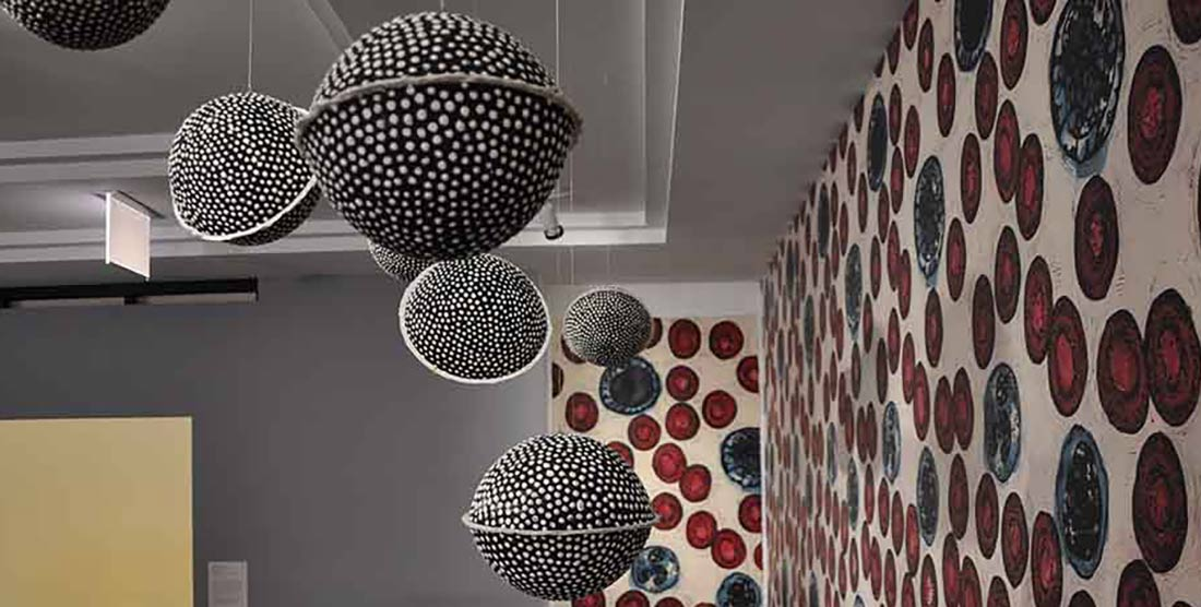 HIV condom-filled pinatas against a background of red blood cell patterned wallpaper by Eric Avery