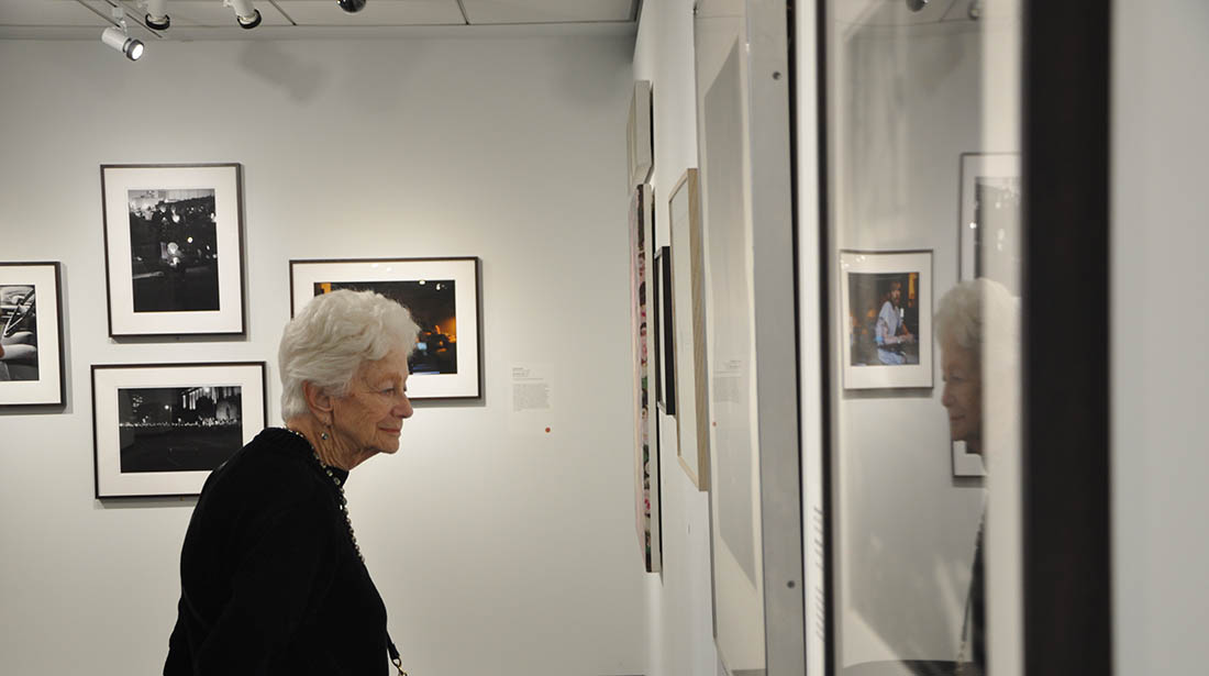 An viewer examines photographs at the new exhibit Art AIDs America.