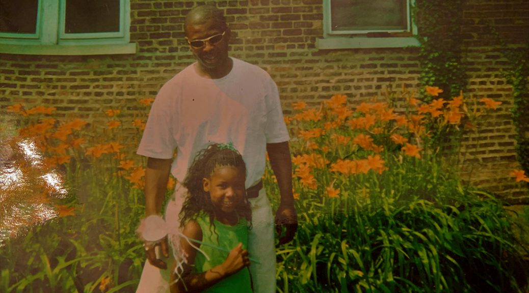 Father stands behind wand-bearing daughter in front of South Shore home.