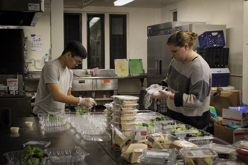 Laine Kaehler and Chris Kim repack salads in preparation for the next delivery shift.