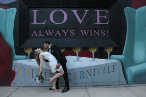 Bride and groom in front of love sign