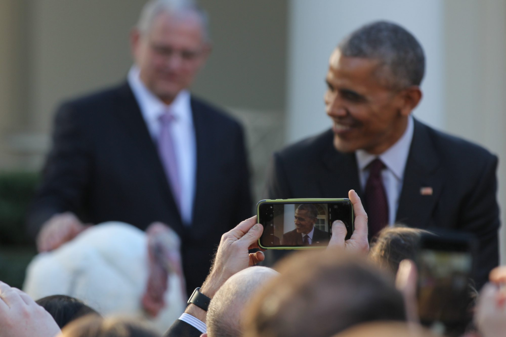 Obama poses with Tot as the crowd eagerly takes photos of them.