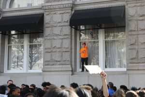 A middle school kid stands on a window sill of the Trump hotel, holding a rainbow flag.