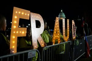 "Members of Herndon-Reston Indivisible, a group created to resist President Trump's policies and elect Democrats to office, held lit-up letters spelling ""Fraud"" and ""Yuge Liar."" (Ester Wells/MNS)"
