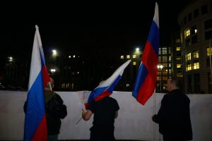 Protestors waved Russian flags as they waited along the sidewalk. (Ester Wells/MNS)
