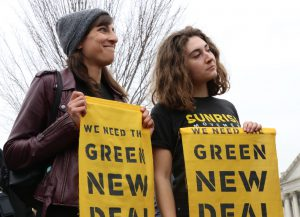"Members of the Sunrise movement held up signs that read, ""We need the Green New Deal,"" as they watched the press conference Thursday. (Dan Rosenzweig-Ziff/MNS)"