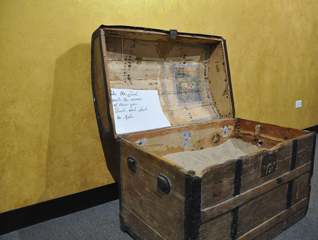 antique wooden chest filled with sand commemorating loved ones lost to AIDs