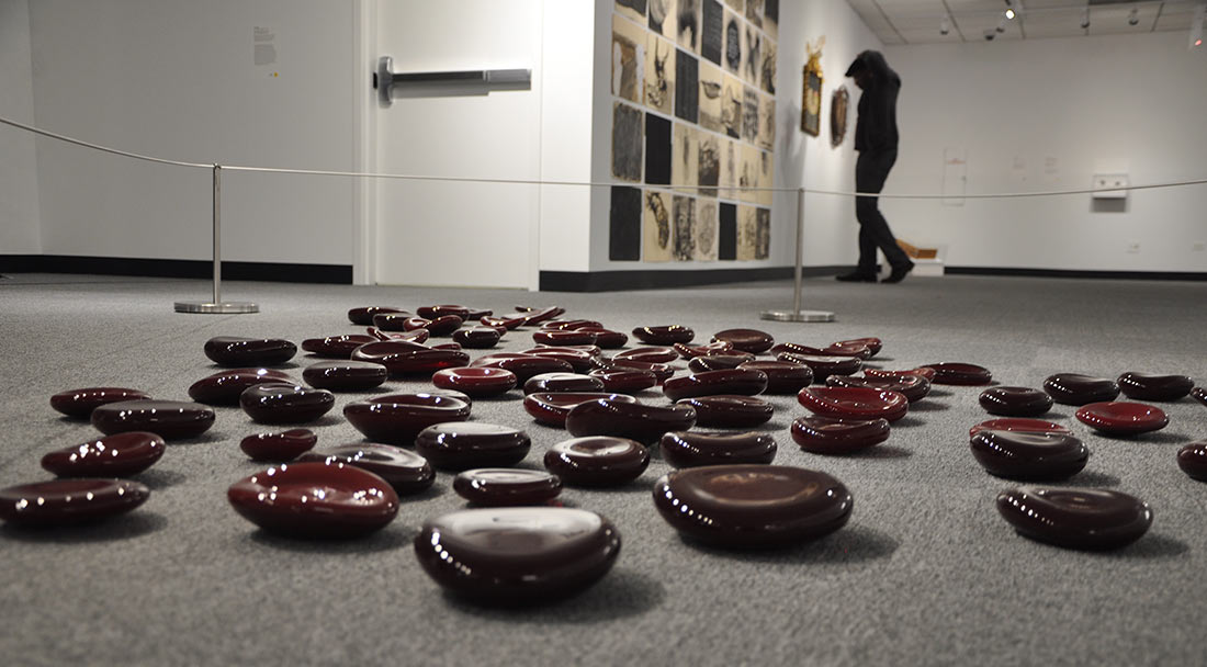 oversized glass red blood cells strewn across the floor in an art gallery