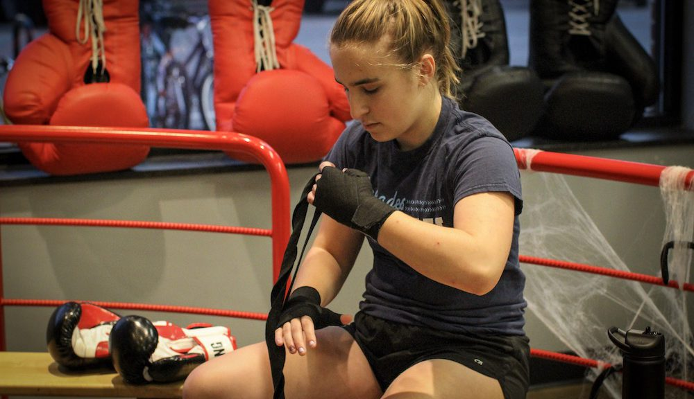Rachel Philips, 20, wraps her hands before the boxing class begins.
