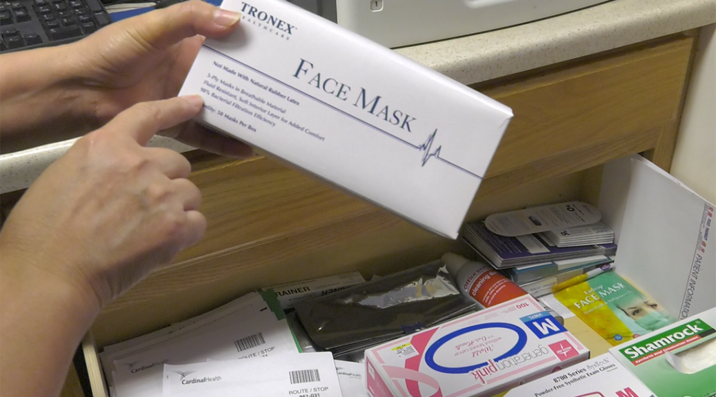 A pharmacy technician holds a box of face masks in a pharmacy in Chinatown