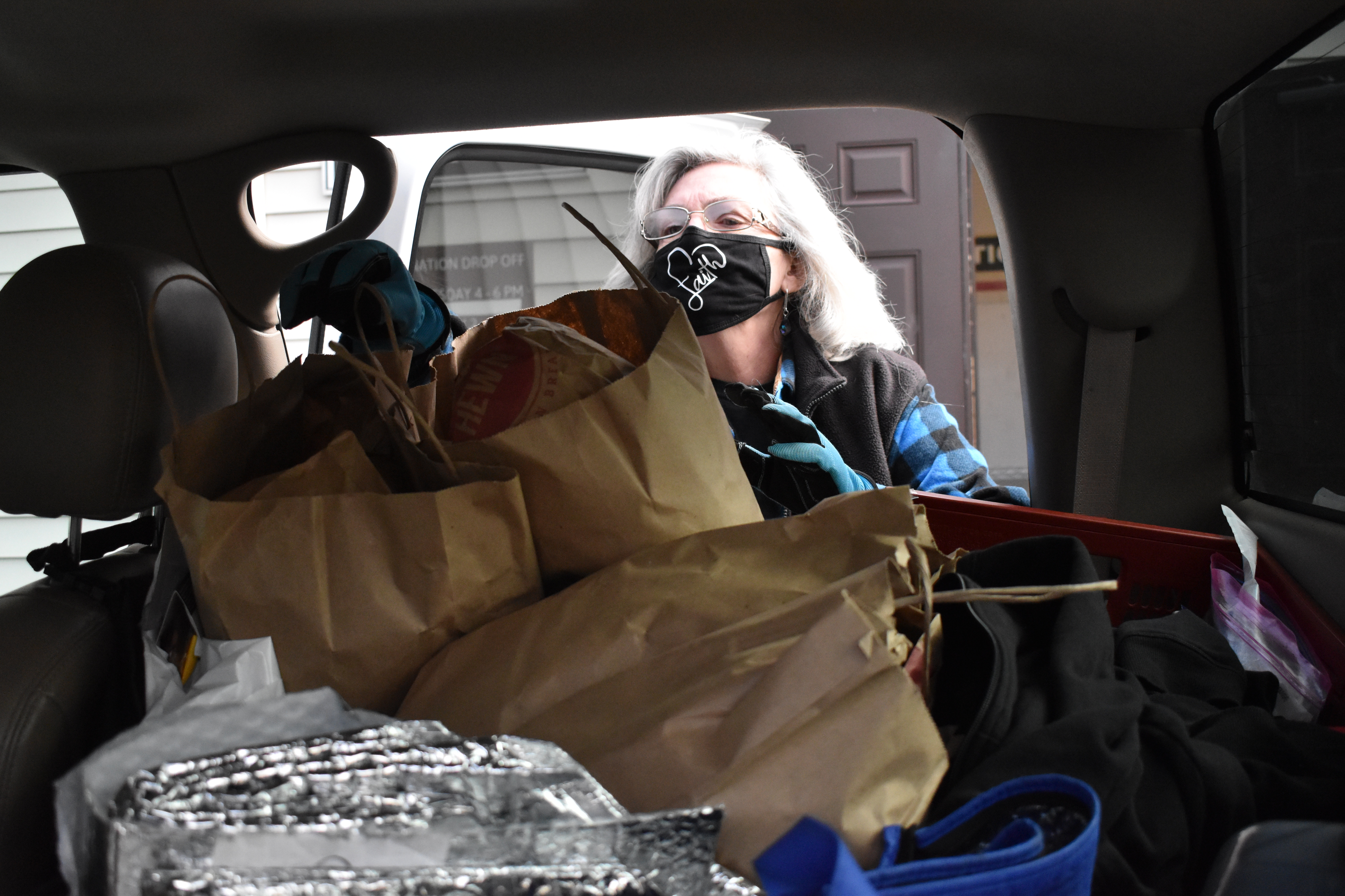 Faith Albano reaches into the back seat of her car to take out bags of bread donations from Hewn and load them into the Hillside Food Pantry.