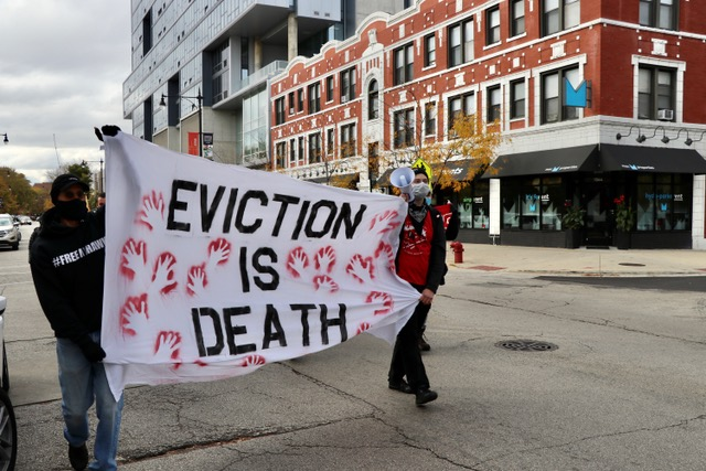 """Activist John Hieronymus marched for tenants' rights with a bullhorn in one hand and a banner in another that read, """"eviction is death."""""""