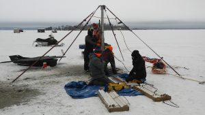 Scientist using instrument to measure for sediment cores on frozen lake