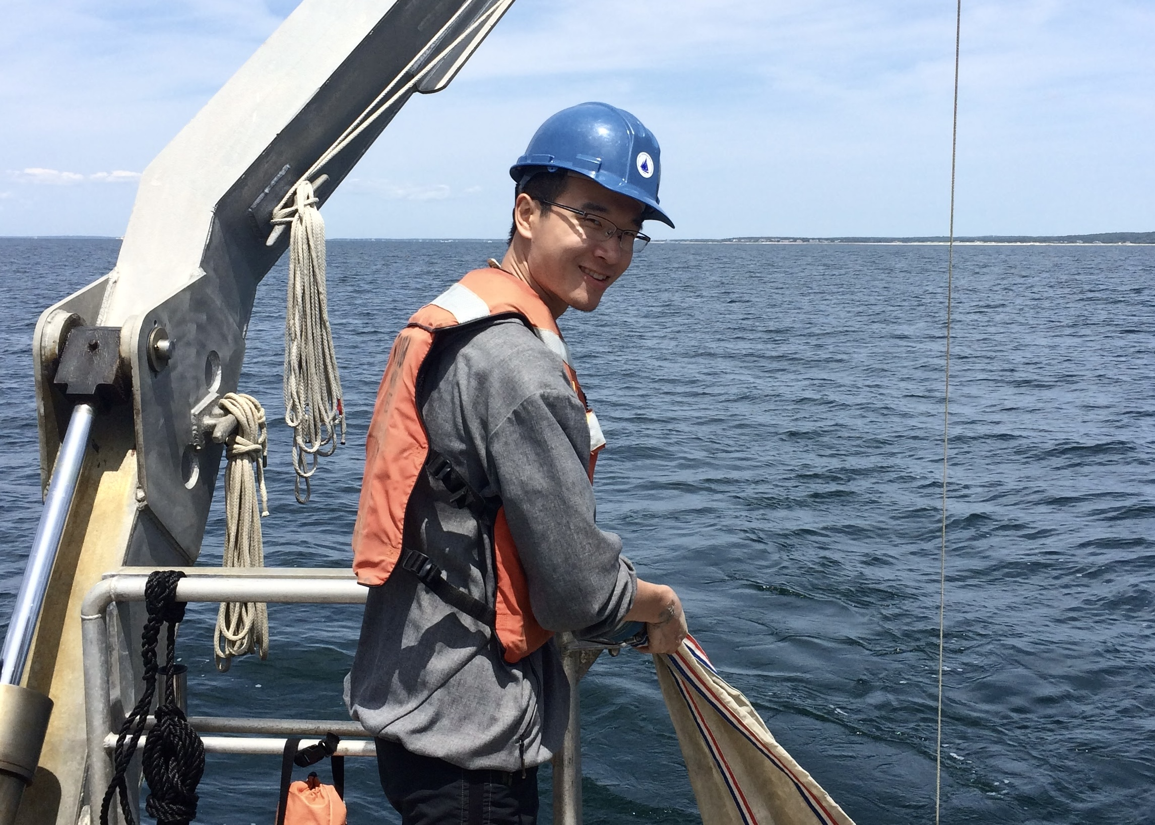 Zhou aboard the R/V Tioga holding a net tow.