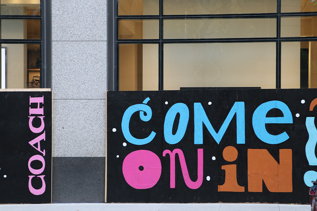 """A colorful handmade """"Come On In"""" sign outside of Coach"""