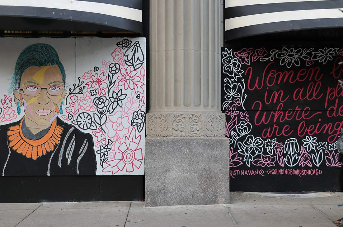 """A sign picturing the late Ruth Bader Ginsburg, along with one of the Supreme Court justice's most iconic quotes, """"Women belong in all places where decisions are being made."""""""