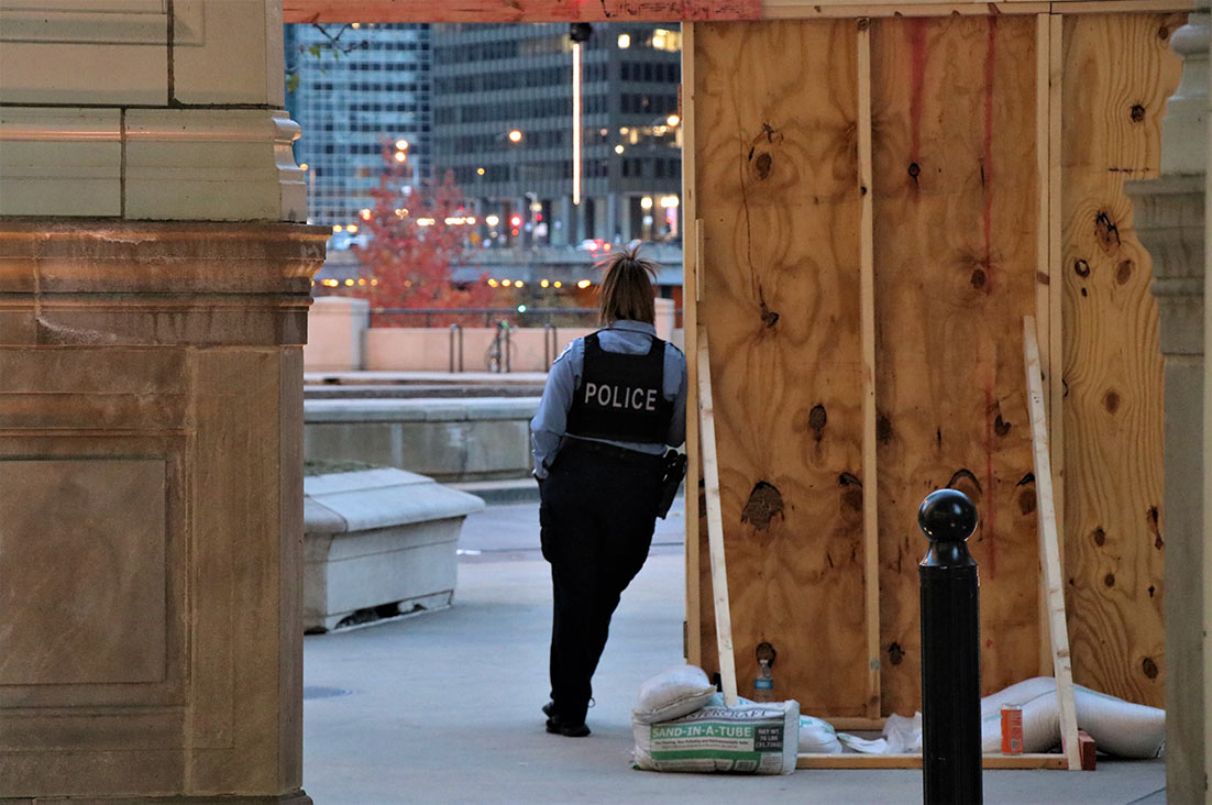 A police officer stands outside a boarded-up Wrigley Building