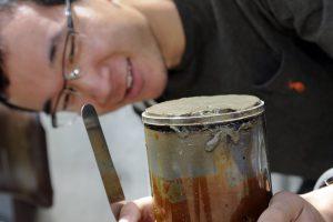 Yuxin Zhou looking at a sediment core, holding a metal spatula.