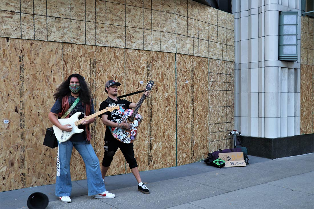 Two musicians use the boards covering an Under Armour as the backdrop for an impromptu concert.