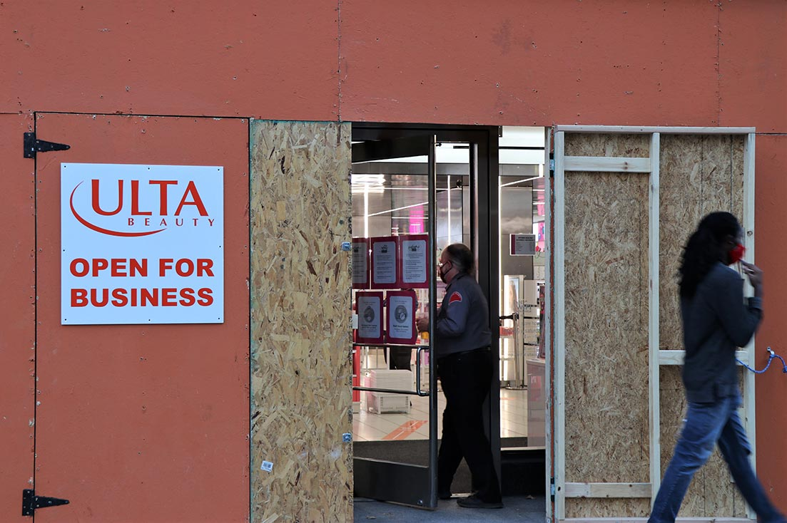 A security guard enters the wooden cave of an Ulta Beauty