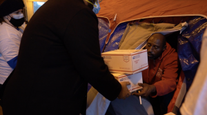 A volunteer gives two care packages to a homeless