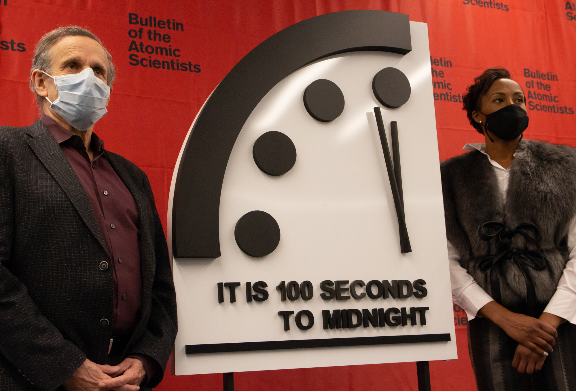 """Robert Rosner and Suzet McKinney stand in front of the Doomsday Clock, which reads """"It is 100 seconds to midnight."""""""