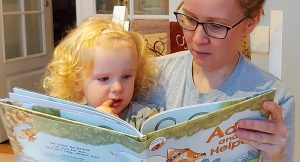 "Three-year-old Esther and her mother, Anne Berit Peterson, read ""Ada and the Helpers"" together."